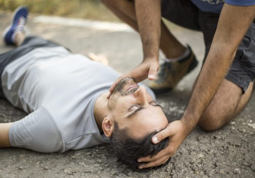 Man gives first aid to a person on the asphalt